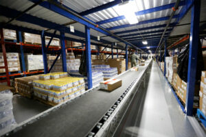 Conveyor moves products in a Pick Module pallet rack system.