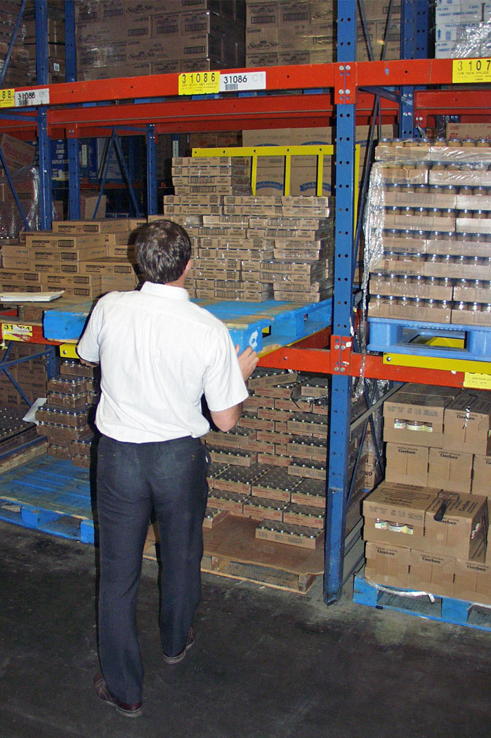 A worker picks product from Frazier's Glide 'N Pick® pallet rack cart.